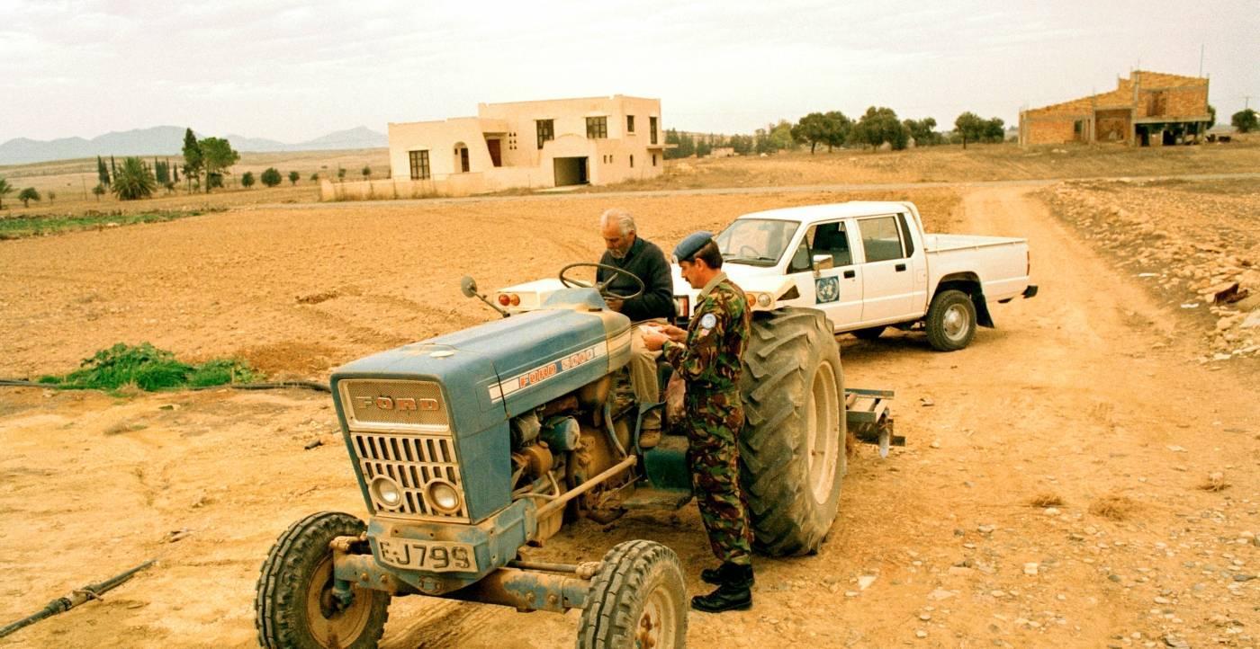 En britisk soldat fra FNs fredsbevarende styrke på Kypros, sjekker identitetspapirene til en kypriotisk bonde på en gammel traktor