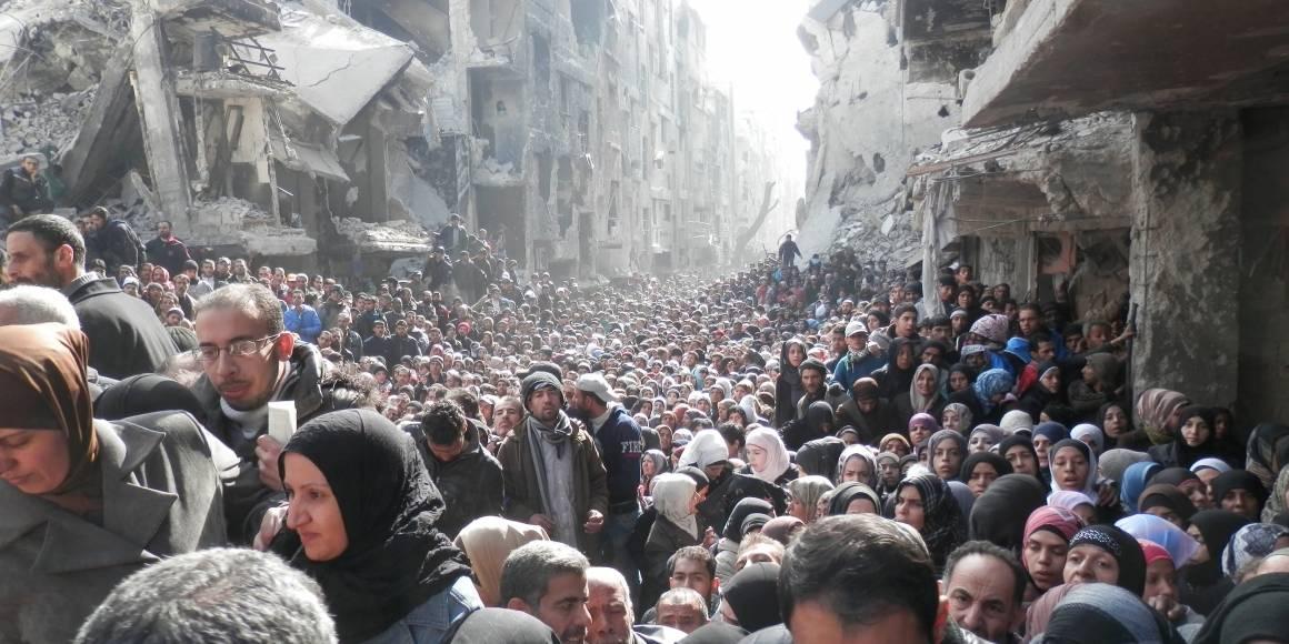 I den palestinske flyktningleiren Yarmouk i Damaskus har tilgangen til mat vært svært begrenset under krigen. Befolkningen står i kø for å få matforsyninger fra FN. (Januar 2014). Foto: Zuma Press/UNRWA