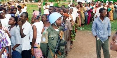 En FN-soldat fra den fredsbevarende styrken holder orden ved et valglokale i Bangui, under valget i 1998. UN Photo/Evan Schneider