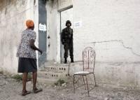 Kvinne på vei til valglokalet i slummen i Bel Air. FN-soldat holder vakt. Foto: UN Photo/Sophia Paris